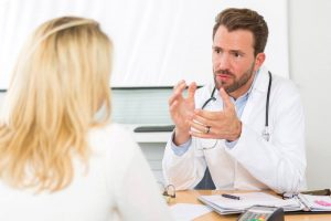 pregnant woman with incontinence talking to doctor